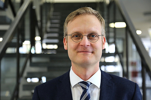 A blond man with glasses, suit and tie stands in front of a staircase and looks into the camera.