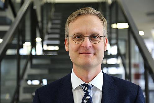 Ein blonder Mann mit Brille, Anzug und Krawatte steht vor einer Stiege und blickt in die Kamera