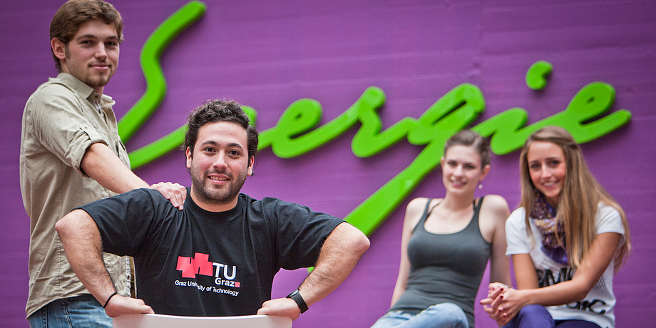 """Two female and two male students of TU Graz in front of a bright green writing saying """"Energie"""" in a building at Campus Inffeldgasse."""