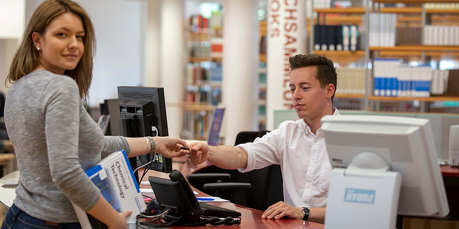 Young woman at the reception desk of a library hands a young man her student ID card.