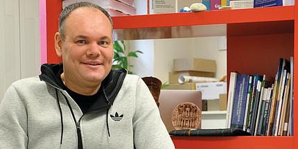 Martin Ebner, Leiter des Bereiches Lehr- und Lerntechnologien an der TU Graz vor einem roten Bücherregal in seinem kunterbunten Kreativ-Büro.