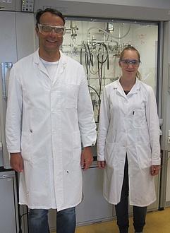 Ein Mann und eine Frau Stehen nebeneinander in einem Chemielabor und tragen einen weißen Mantel und Schutzbrillen
