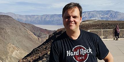 Ein Mann in einem schwarzen T-Shirt steht vor einer Landschaft aus sanften Hügeln.