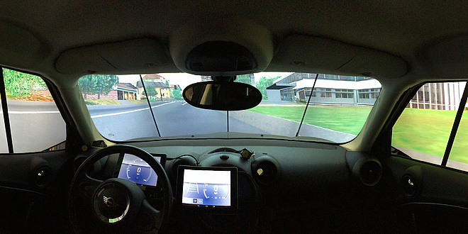 A view from the car cockpit, in the middle there is a tablet PC that functions as an instrument panel. The landscape behind the side windows and the windshield is virtual.