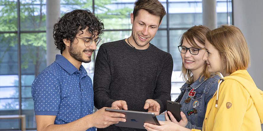 Vier Studierende schauen auf ein Tablet.