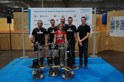 Team GRIPS gained third place in the Logistics League of RoboCup2016 and poses with three logistics robots