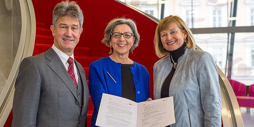 Zwei Rektorinnen und ein Rektor halten den unterzeichneten Letter of Intent in die Kamera