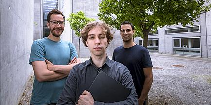 Daniel Gruss steht im Vordergrund und hat einen geschlossenen Laptop in der Hand. Er trägt ein schwarzes Hemd und blonde Haare. Links hinter ihm steht Moritz Lipp, der eine Brille, Bart und ein türkises Shirt trägt. Rechts dahinter steht Michael Schwarz, der kurze schwarze Haare und ein schwarzes Shirt trägt.