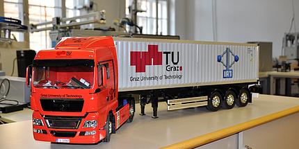 Ein Modell-Lkw mit rotem Führerhaus und weißem Container mit TU Graz Logo steht im Testlabor auf einem Tisch