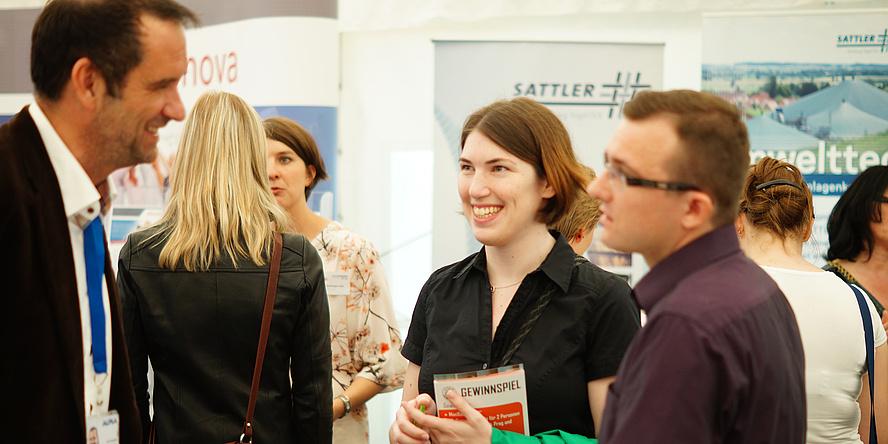 Eine junge Frau und ein junger Mann im Gespräch mit einem Firmenvertreter mittleren Alters mit Krawatte auf der TECONOMY Graz. Im Hintergrund weitere Besucherinnen vor Infoständen von Unternehmen.