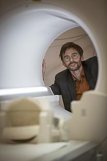 A man looks into the camera through an MRI examination tube.