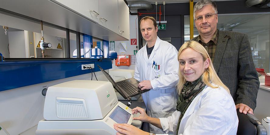 Zwei Männer und eine Frau mit Laborgerät