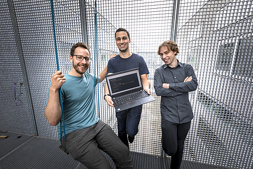 Three men stand on a veranda secured with lattice walls; the left man sits in a swing, the middle man holds a laptop in his hands r Swing, in the middle