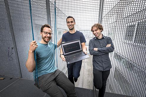 Drei Männer stehen auf einer Veranda, die mit Gitterwänden gesichert ist; Der linke Mann sitzt in einer Schaukel, der mittlere Mann hält einen Laptop in Händen r Schaukel, in der Mitte