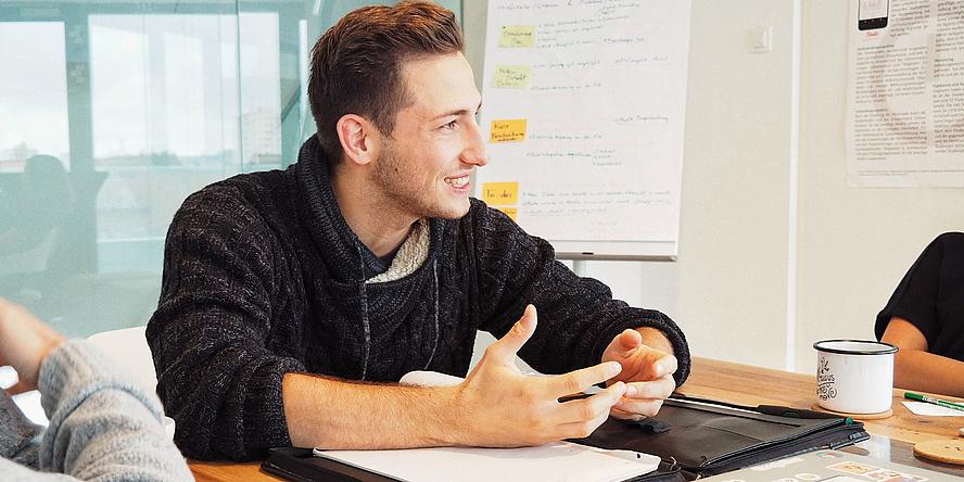 Junger Mann in einem Meeting.