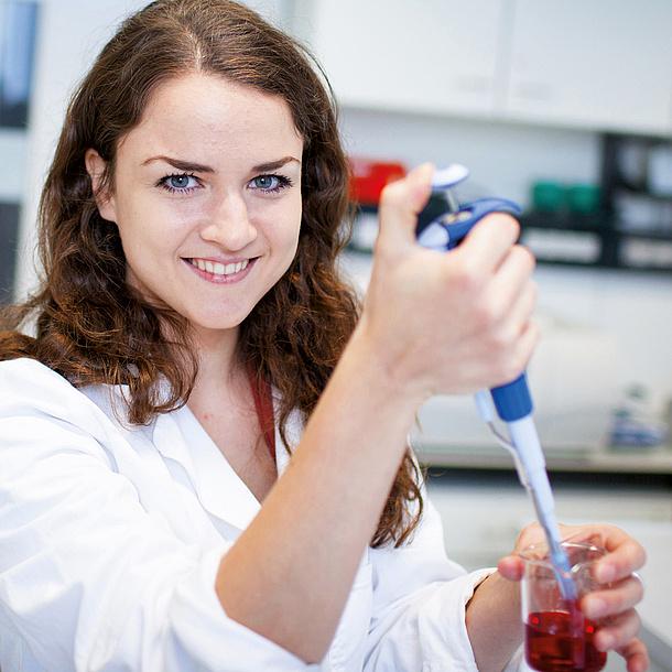 Eine junge Frau entnimmt aus einem Glas eine Probe einer roten Flüssigkeit. Bildquelle: Grumet - BioTechMed