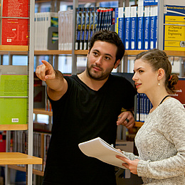 Man showing a woman the way in the library. Photo source: Lunghammer - TU Graz