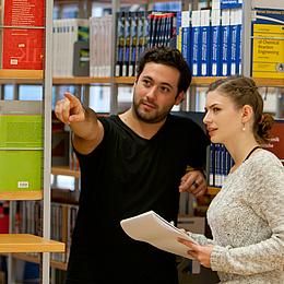 Ein Mann zeigt in einer Bibliothek einer Frau den Weg. Bildquelle: Lunghammer – TU Graz