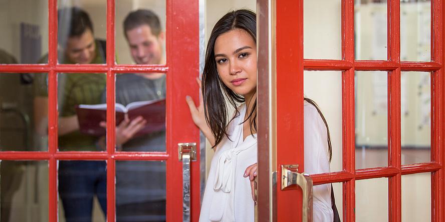 Junge Frau im Türspalt einer halb geöffneten Glastür mit roten Verstrebungen, im Hintergrund sind durch die Tür zwei lachende junge Männer zu erkennen, die in ein Buch schauen.