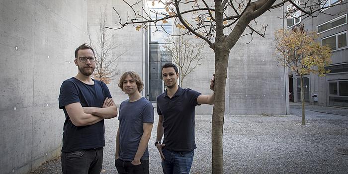 Drei junge Männer stehen im freien zwischen Gebäuden und Beton. Einer lehnt an einem Baum, der keine Blätter mehr trägt.