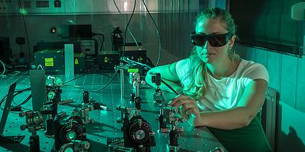 Eine Frau an einem Laborgerät in grünes Licht getaucht