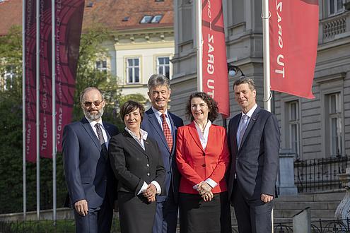 Das Rektoratsteam - zwei Frauen und drei Männer stehen vor der Technischen Universität, im Hintergrund sind die TU Graz-Fahnen zu sehen