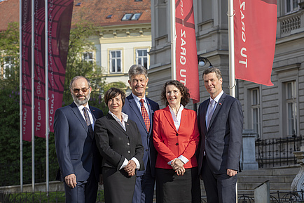 The Rectorate team - two women and three men stand in front of TU Graz, flags can be seen in the background.