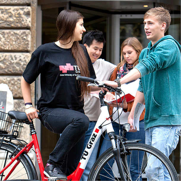 Woman wearing a shirt of TU-Graz on a bicycle, talking to several people. Photo source: Lunghammer - TU Graz