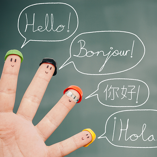 "Four fingers in front of a board, which displays faces which wear different sorts of hats. The board says ""Hello"" in different languages. Photo source: lemontreeimages - fotolia.com"