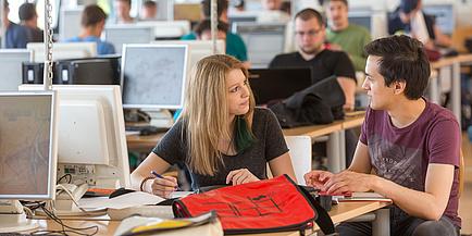 Zwei Studierende der TU Graz - ein Junge und ein Mädchen - unterhalten sihc an einem Computerarbeitsplatz in einer universitären Lernumgebung.