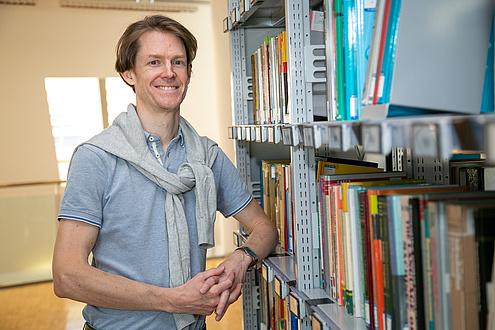 TU Graz-Forscher vor einem Bücherregal