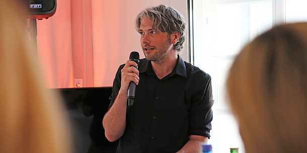 Forscher Tony Ross-Hellauer steht in einem schwarzen Hemd in der Bildmitte, er spricht in ein Mikrofon, das er in der rechten Hand hält. Im Vordergrund sind unscharf die Köpfer zweier Zuhörerinnen zu sehen.