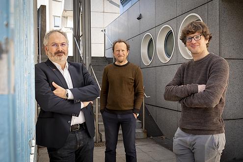 Drei freundlich blickende Männer