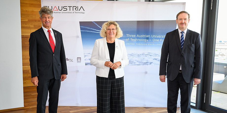 Zwei Männer und eine Frau vor einer Fotowand