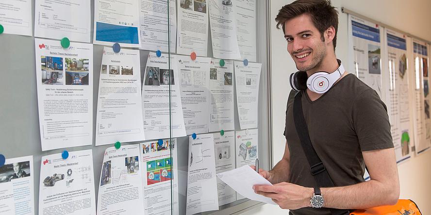 Ein Student mit rotem Notitzbuch und grauem T-Shirt, eine Studentin mit weißer Bluse und ein Student mit schwarzem Kapuzenpulli beschäftigen sich im Freien vor dem Eingang zu einem TU-Graz-Gebäude gut gelaunt mit einem Notebook, das die Studentin hält