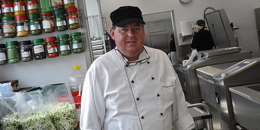 Martin Grabenhofer in white chef's uniform and black cap in front of a shelf bearing colourful spice jars and bags of chopped vegetables in the kitchen of the Inffeldgasse canteen.