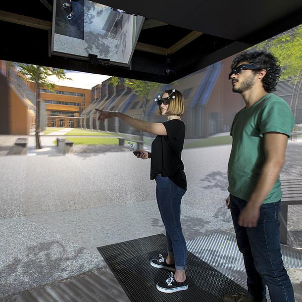 Zwei Studierende mit 3D Brillen stehen in einem virtuellen Raum.