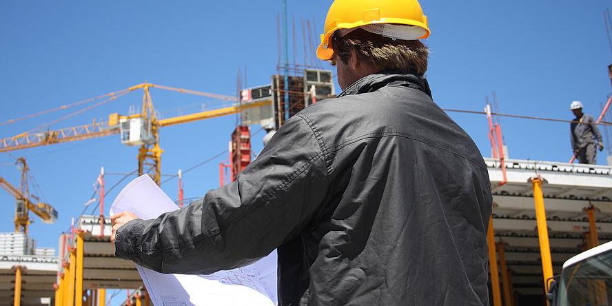 Mann mit gelbem Helm und grauer Arbeitsjacke mit dem Rücken zur Betrachterin oder Betrachter gedreht, vor einer Baustelle mit zwei Kränen schaut in einen Bauplan.