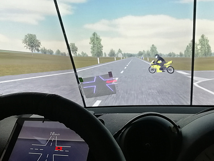An intersection on an open country road is shown from the cockpit perspective; a yellow motorcycle is approached from the right; a display is to be found on the windscreen showing the intersection and the motorcycle as a red dot; the intersection is also shown virtually on the instrument panel behind the steering wheel.