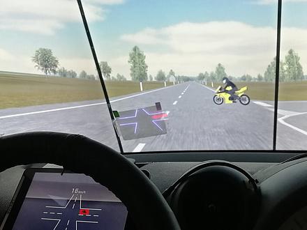 Eine Kreuzung auf einer Freilandstraße wird aus der Cockpitperspektive gezeigt, von der rechten Seite kommt ein gelbes Motorrad angefahren; An der Windschutzscheibe ist ein Display zu sheen, das die Kreuzung und das Motorrad als roten Punkt abbildet; Auch am Instrumentenbrett hinter dem Lenkrad wird die Kreuzung virtuell angezeigt.