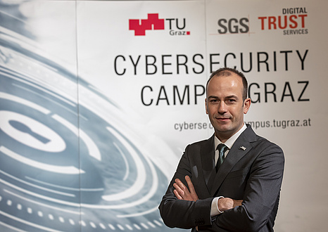 A man in a suit stands in front of the expo wall of the Cybersecurity Campus Graz