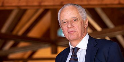 Porträt eines Mannes mit schwarzem Anzug und Krawatte, im Hintergrund Holzdachstuhl und Trams
