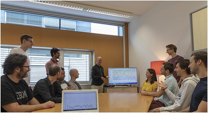Mehrere Personen sitzen an einem Tisch. In der Mitte ist ein Computerbildschirm mit mehreren Kurven.