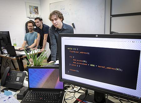 Rechts vorne ist eine Schreibtischsituation zu sehen - Am Bildschirm ist ein Computercode abgebildet, links hinten sitzen zwei Männer, ein dritter Mann steht daneben.