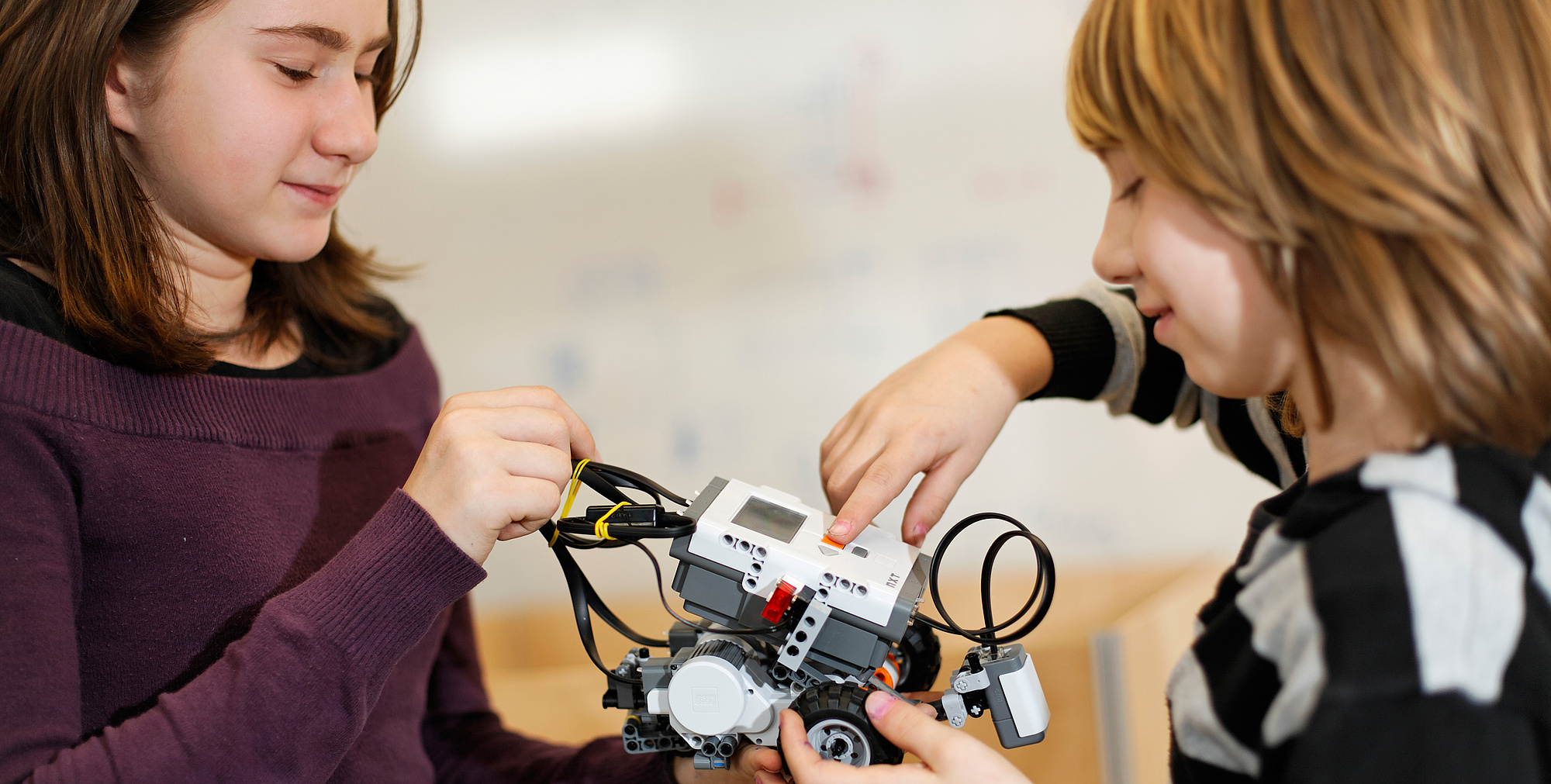 Two kids working on a robot.
