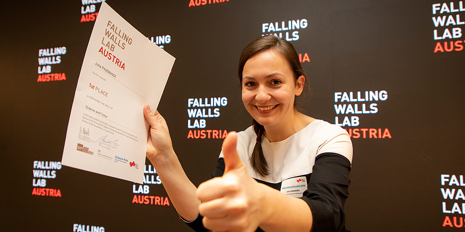 Eine junge Frau lächselt in die Kamera und hält in der einen Hand eine Urkunde und den Daumen der anderen Hand hoch