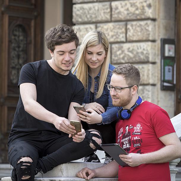 Drei Studierende mit Smartphones.