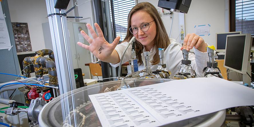 Forscherin in weißem Kittel, Hand mit Tattoo-Sensor und Laborequipment