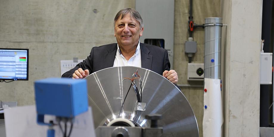 Christian Moser steht vor einem silbernen Metallgestell.