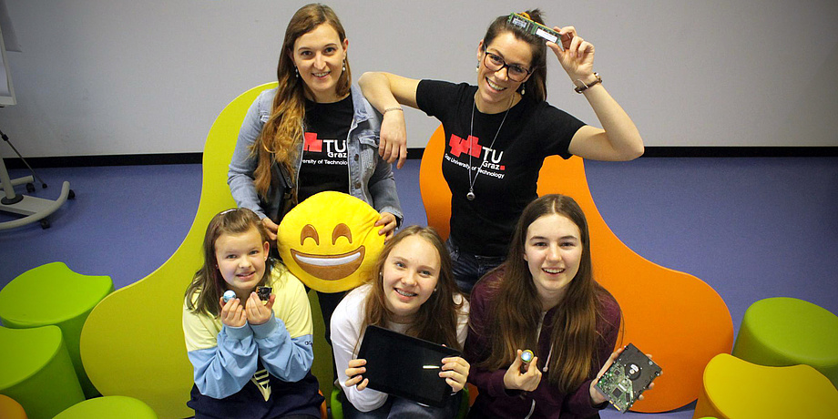 Vier Mädchen im Schulalter von 10 bis 14 Jahren und eine Frau mit Brille präsentieren jeweils eine Computerplatine, ein Tablet und einen drei Zentimeter großen kugelförmigen Roboter.